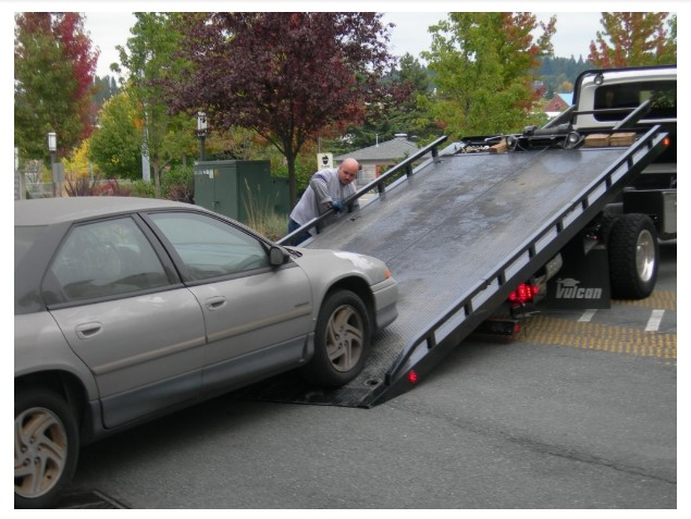 Picture of a car being loaded onto a tow truck from the Rambling Wrecker Manassas VA
